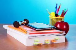 Great reference book and other educational things. The book, hourglass, e-book, pencils and handles in a support, an apple on a table Royalty Free Stock Image