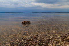 Great Russian River Volga, a cloudy summer day. The stones shine through the water Stock Images