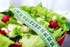 Great salad. Red bowl with salad on the table in the kitchen with meter to measure waist stock photography
