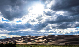 Great Sand Dune National Park Colorado Natural Wonder Sun Beams. Showing through the clouds as the contrast builds over the dunes. The desert landscape of this royalty free stock photo