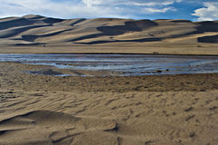 Medano Creek flowing in front of the Great Sand Du. Medano Creek in the mid ground at the Great Sand Dunes National Park in southern Colorado Royalty Free Stock Images