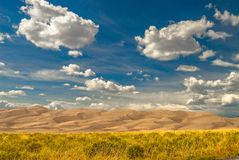 Great Sand Dunes National Park. White puffy clouds in the desert of Colorado royalty free stock images