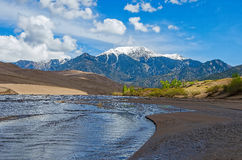 Great Sand Dunes. River bed at the Great Sand Dunes with the Colorado Rocky Mountains in the background Royalty Free Stock Photos