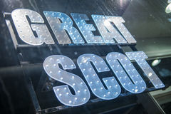Great Scot. An illuminated sign of Great Scot is shot in a window with the tracks of raindrops. Could be used as an illustration to Scotland independence topics Stock Photos