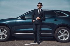 Great sense of style. Full length of handsome young businessman smiling while standing near his car outdoors stock photography