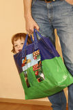 Great shopping. Little girl handled in a big shopping bag Royalty Free Stock Image