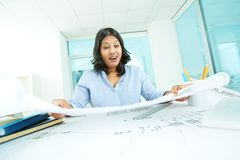 Great sketch. Portrait of mature businesswoman looking at project with surprise in office Stock Photos