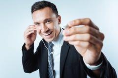 Cheerful joyful man sharing his headphones Stock Photography