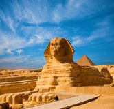 Great Sphinx Body Blue Sky Pyramid Giza Egypt. Full length body profile of Great Sphinx including head, feet with great pyramid of Menkaure in background on a Stock Image