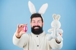 The great spring festival of Easter. Bearded man with bunny toy and Easter egg. Celebration of spring time. Hipster with. Long rabbit ears holding egg laying royalty free stock image