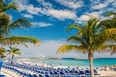 Great stirrup cay, Bahamas - January 08, 2016: sea beach, people, chairs, green palm trees on sunny day. Summer vacation. Holidays, relax. Wanderlust travel royalty free stock image