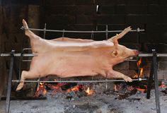Great stuck pig that cooks slowly on steel spit in the gigantic. Stuck pig that cooks slowly on enormous steel spit in the gigantic fireplace Royalty Free Stock Photo