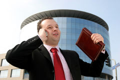 Great success in business. Happy young businessman talking on a cell phone and holding a notebook in front of a corporate building Stock Image