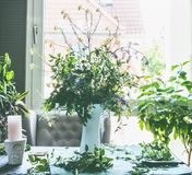 Great summer wild flowers bunch in white vase on table in living room at window . Home lifestyle royalty free stock photography