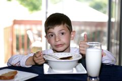 Great taste. 6 year old boy having breakfast in the morning stock image