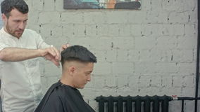 Great time at barbershop. Cheerful young bearded man getting haircut by hairdresser stock footage