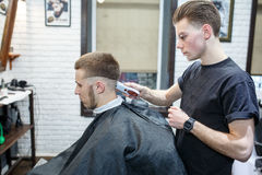 Great time at barbershop. Cheerful young bearded man getting haircut by hairdresser while sitting in chair at barbershop Royalty Free Stock Photography