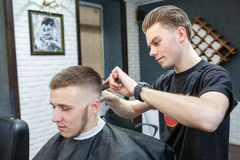 Great time at barbershop. Cheerful young bearded man getting haircut by hairdresser while sitting in chair at barbershop royalty free stock photos