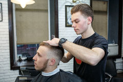 Great time at barbershop. Cheerful young bearded man getting haircut by hairdresser while sitting in chair at barbershop Royalty Free Stock Photo