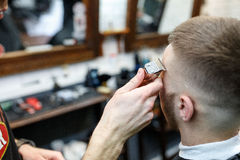 Great time at barbershop. Cheerful young bearded man getting haircut by hairdresser while sitting in chair at barbershop stock photo
