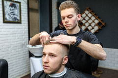 Great time at barbershop. Cheerful young bearded man getting haircut by hairdresser while sitting in chair at barbershop stock photography
