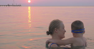 Great time with mom on vacation. Family vacation on the coast. Cheerful son and young mother bathing in the sea at sunset, they talking and embracing in water stock video footage