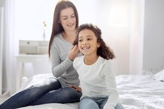 Alert mother making a hairdo for her daughter. Great time together. Nice joyful curly-haired girl smiling and her mother sitting behind her and making a hairdo Royalty Free Stock Image