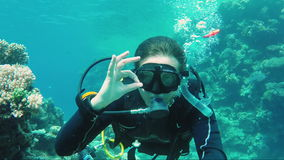 Great vacation and diving in the warm sea. The scuba diver signs the okay sign and takes himself off on a video of Self. Excellent vacation and diving in the stock video