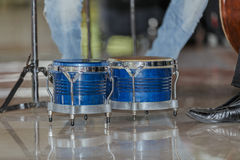 Great  view of blue wooden bongos standing on shiny marble floor, surrounded by people legs Royalty Free Stock Photo