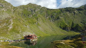 Great view of mountain cottage on alpine lake shore. Superb green mountain valley with a cottage on alpine lake shore Royalty Free Stock Images