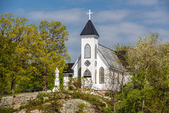 Great view of old vintage white church standing on a rock cliff in woods Stock Image