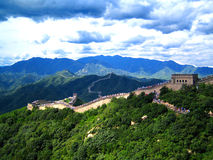 Great Wall of China. Between the forest during summer with lots of people walking over it. Cloudy sky and mountains in the background Royalty Free Stock Photos