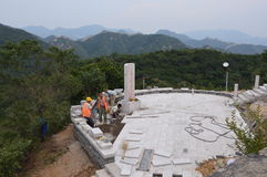 Great Wall of China. This very unique photograph depicts construction workers building  a structure next to the Great Wall of China. The Great Wall can be seen Royalty Free Stock Image