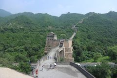 The Great Wall. View of the Great Wall of China. People visiting in the heat. Shades of green contrast against the stoney wall that stretches into the distance royalty free stock images