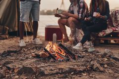 Great warm evening. Close up of young people eating roasted marshmallows while camping near the lake stock photo