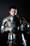 Great warrior with sword and heavy armour. Knight holding his helmet and sword Stock Photos