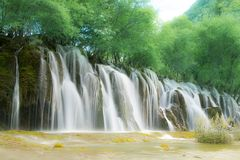 Waterfall of Jiuzhai valley. The great waterfall is a gorgeous sightseeing in Jiuzhai valley where always has numerous tourist taking photo along with the wide Stock Image