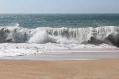 Great waves, storm, the Atlantic Ocean, Portugal. Big stormy waves crashing over Portuguese Coast - enhanced sky stock image
