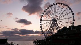 The great wheel and jet airplane flying across the sky over Puget Sound at sunset, Seattle, Washington, USA stock video
