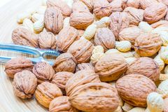 Great wooden bowl full of different nuts and a nutcracker royalty free stock photography