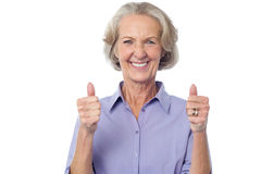 Great work, keep it up!. Smiling old lady showing double thumbs up Stock Photo