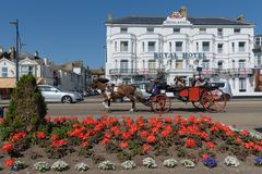 GREAT YARMOUTH, UNITED KINGDOM - JULY 14, 2018 - Horse and cart. With tourists passing the Royal Hotel on Great Yarmouth sea front stock images