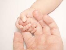 Greater Assurance. Baby fingers grabbing mother's finger Stock Photo
