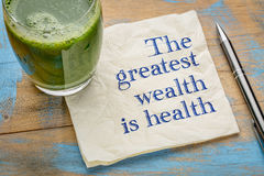 The greatest wealth is health. Advice or reminder - handwriting on a napkin with a glass of fresh, green, vegetable juice Royalty Free Stock Photography