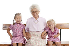 Greatgrandmother and greatgrand children. Great-grandmother and great-grandchildren sitting on a bench Royalty Free Stock Photo