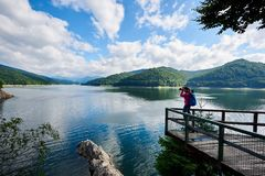 Young female photographer makes picture of amazing Vidraru lake and green rocky mountains. Greatness of nature. Young female photographer makes picture of Royalty Free Stock Photos