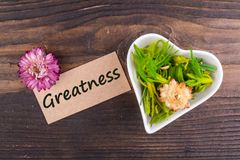 Greatness word on card. With dried flower and heart shape bowl on wood Stock Photos