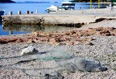 Grebaštica, Croatia, fisherman net on the beach. Grebaštica, near Šibenik, Croatia, detail of bay  with fisherman nets drying on the beach Royalty Free Stock Photo