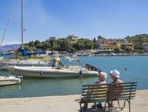 Grecia, Corfú, Kassiopi 28 de septiembre de 2018: Turista mayor de dos pares de la gente que se sienta en banco en Quay con la vi imagenes de archivo