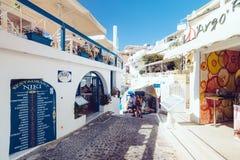 Grecia, Santorini - 1 de octubre de 2017: gente vacationing en las calles estrechas de las ciudades blancas en la isla Fotos de archivo libres de regalías